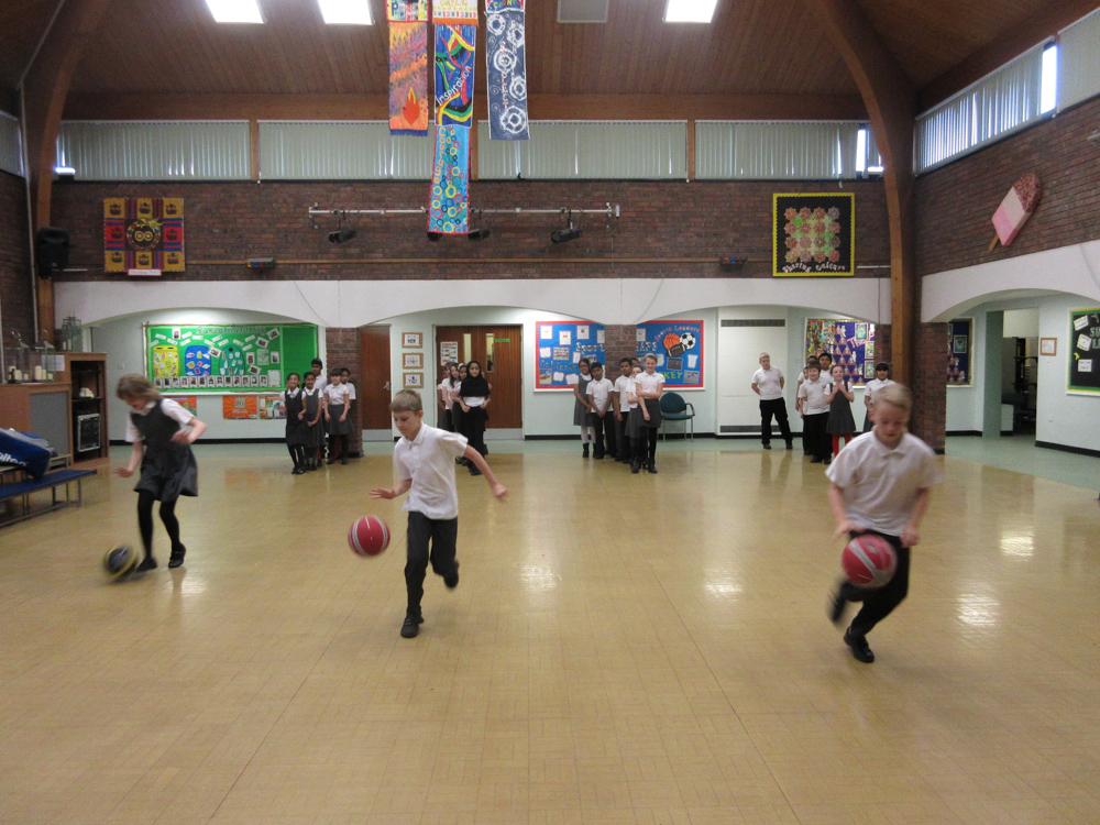 The children practicing basketball skills