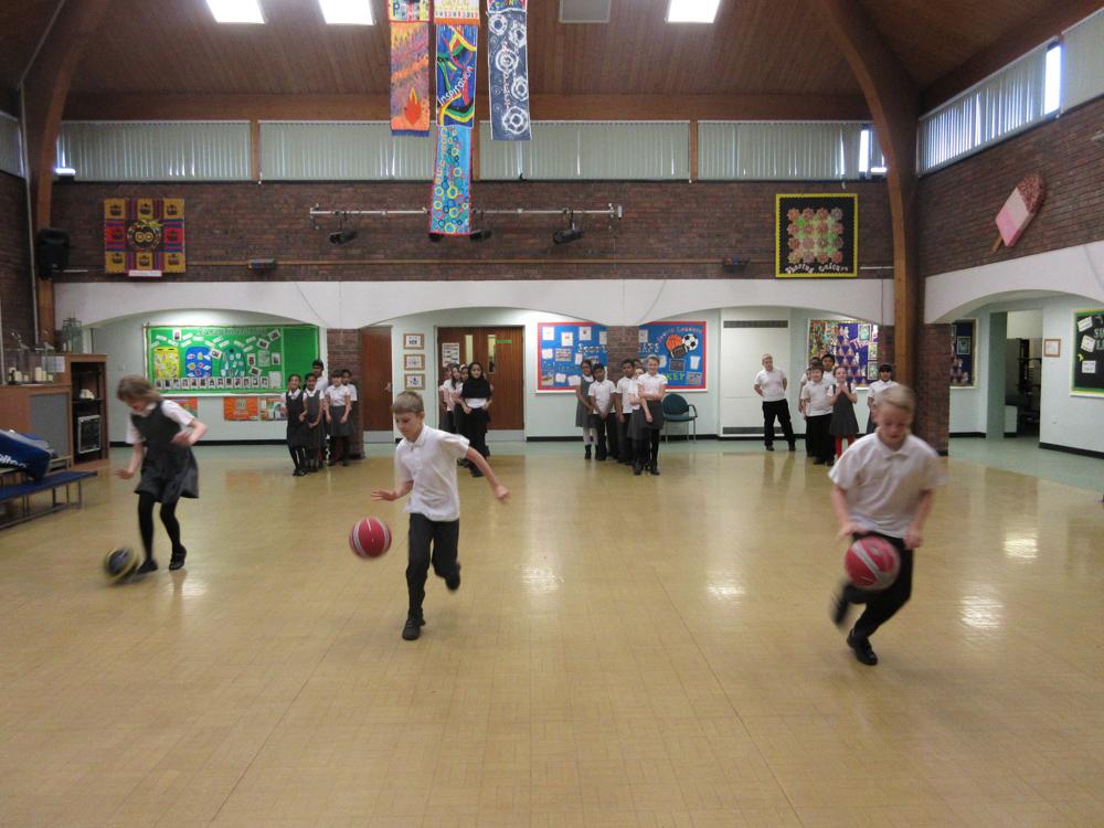The children practicing basketball skills