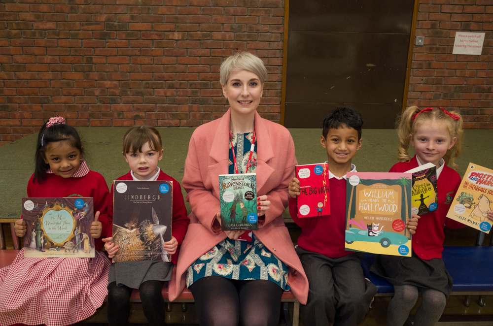 Lauren from First Class Supply with the books donated to the library
